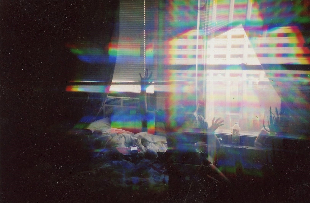 white woman sitting in front of window with rainbow prisms around her