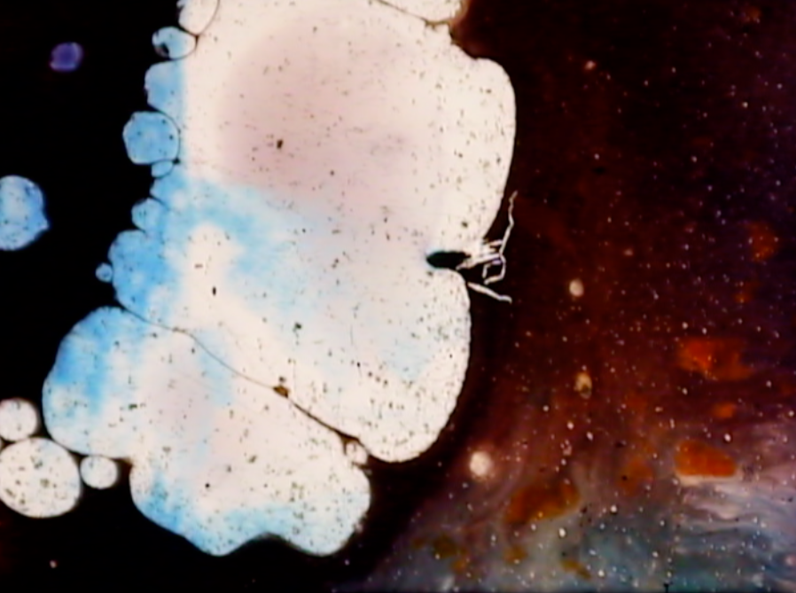 abstract image of white blobs in front of blue, black, and orage colored hues