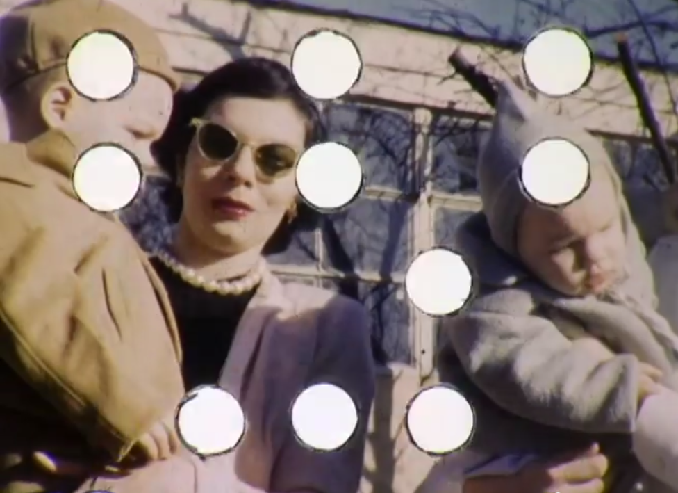 white woman in sunglasses and pearls with two small children posing in front of windows