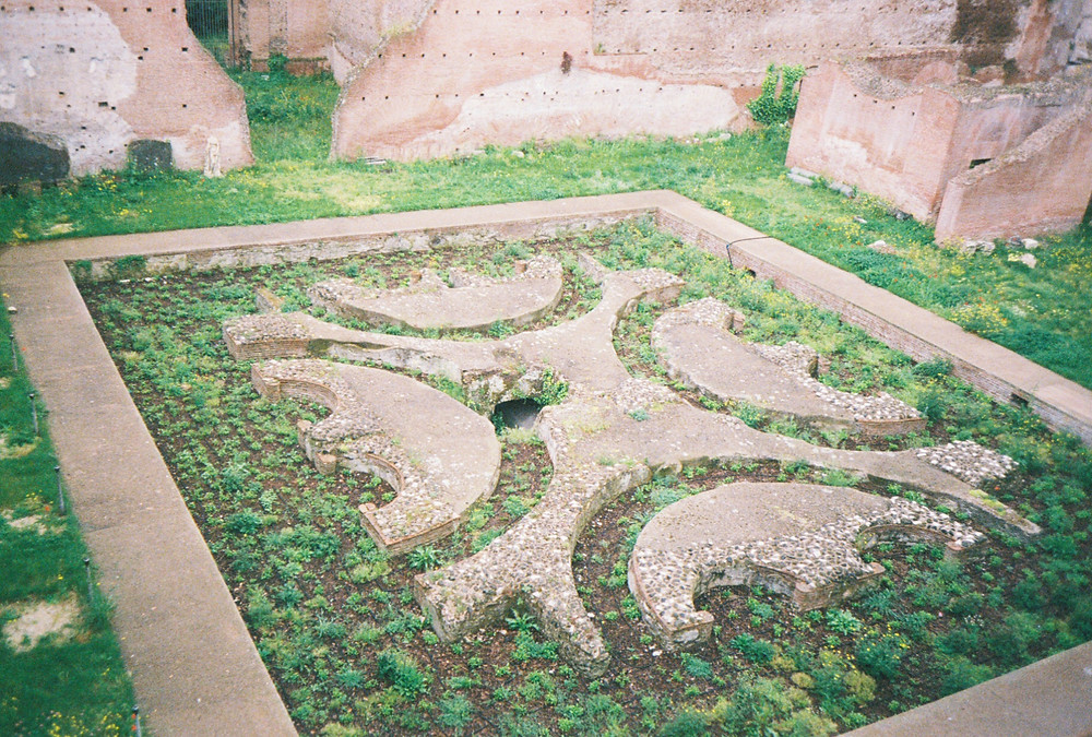 Roman ruin of flat geometric shapes with green grass and small plants growing next to it