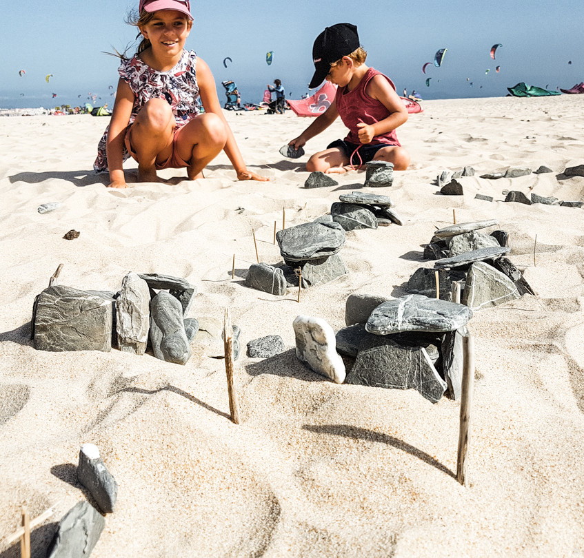 Les enfants construisent un village avec des cailloux et des bâtons