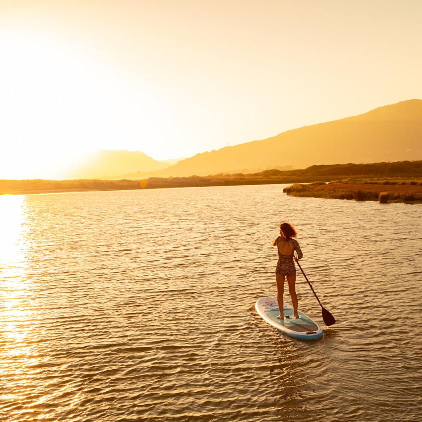 Marie fait du paddle dans les rayons du soleil couchant