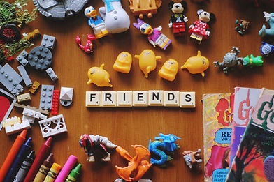 """A variety of toys laid out on a table. In the center, Scrabble tiles spell out """"friends"""""""