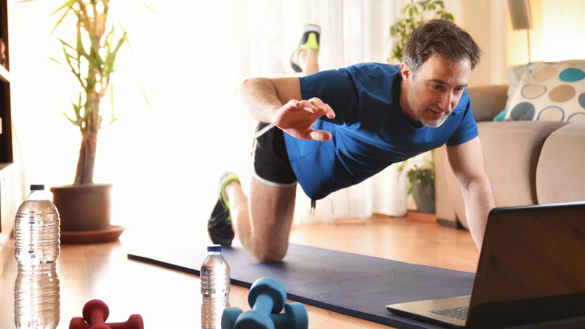 Man doing sports on a mat watching video