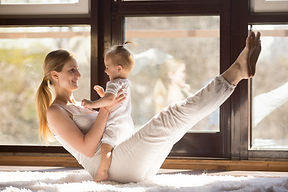 Young yogi smiling mother working out en