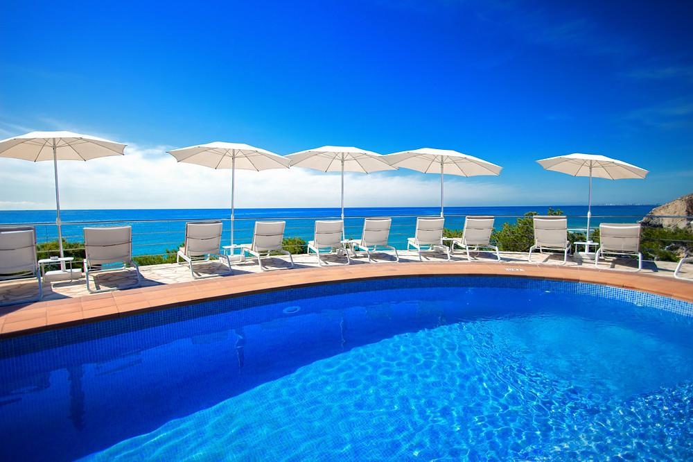 terrasse sur la mer avec piscine et transats