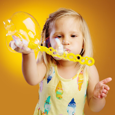 Portrait of toddler blowing bubbles by clifton photographic