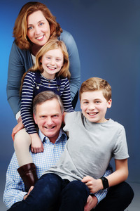 Portrait of family in coordinating blue outfits by clifton photographic