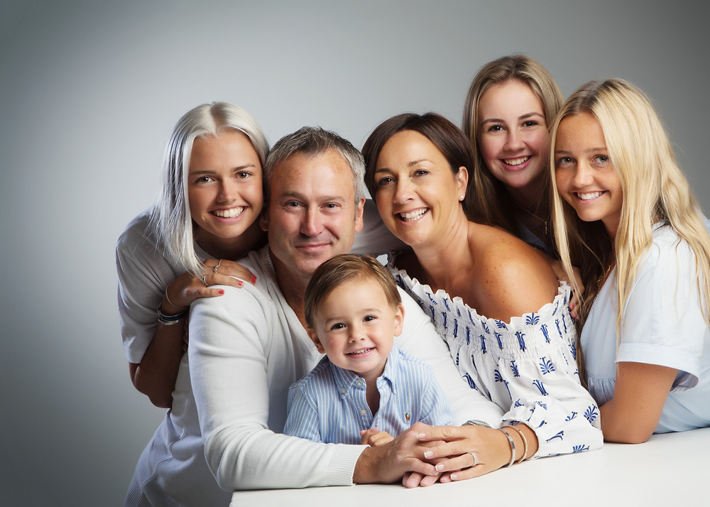 Family wearing coordinating outfits with neutral tones by clifton photographic