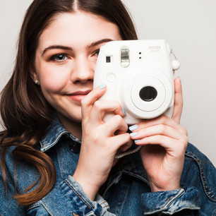 Teenager with instax camera by Clifton Photographic
