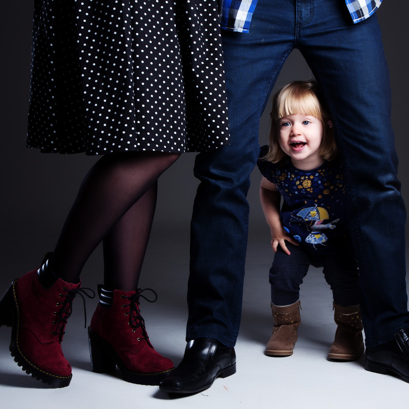 Young child posing through parents legs photographed by clifton photographic