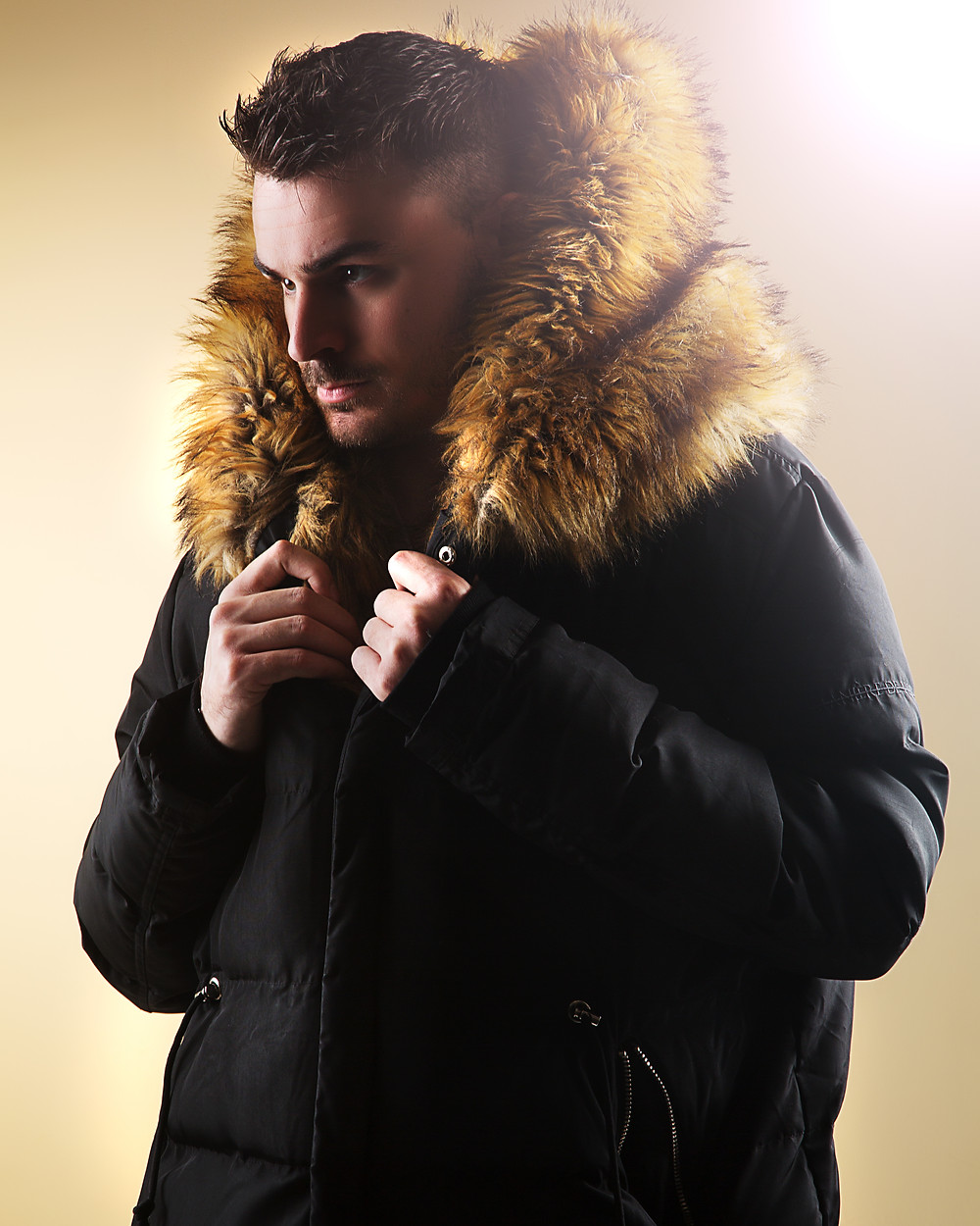 Professional portrait of man in a big hooded coat