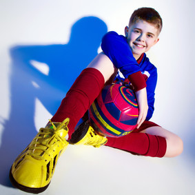 Young footballer with yellow shoes by Clifton Photographic