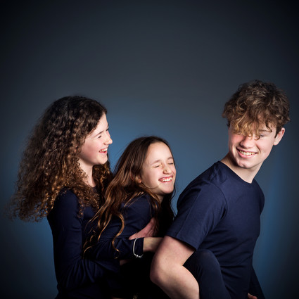 Portrait of laughing brother and sisters by Clifton Photographic