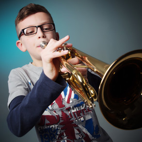 portrait of boy playing trumpet by Clifton Photographic