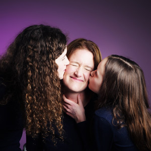 daughters kissing mum on the cheek by Clifton Photographic