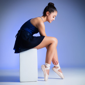 Portrait of young ballet dancer tying shoes by Clifton Photographic
