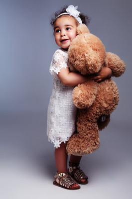 Young child cuddling big teddy photographed by clifton photographic