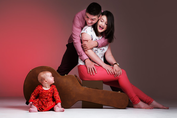 Family wearing red outfits sat on guitar case by Clifton Photographic in Bristol, Uk