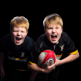 twins with a rugby ball by Clifton Photographic