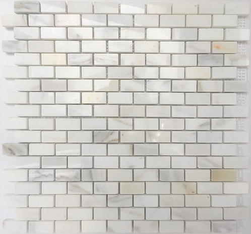 Calacatta mini subway stone tile is rich with colours of golds, greys and browns on a pristine white background