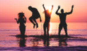 Happy friends jumping inside water on tr