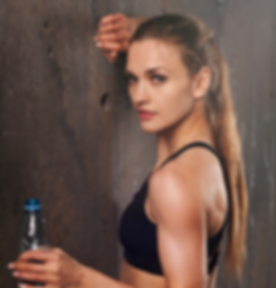 Young athletic woman in sportswear drinking water in studio against black background. Ideal female s