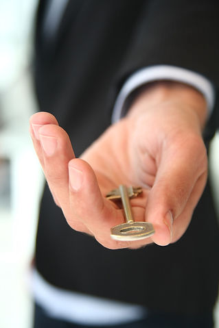 Picture shows a key in a nicely groomed hand, symbolizing the opening of a rental mailbox and a new relatioship.