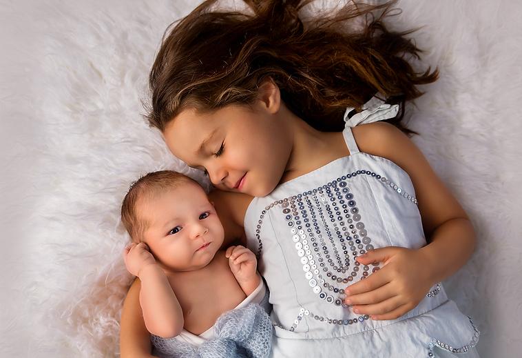 Newborn baby boy with his big sister.