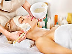 Woman with clay facial mask in beauty sp