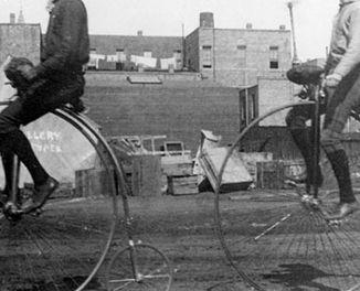 zwart-witfoto van twee mannen op een hoge bi aka een fiets met groot voorwiel