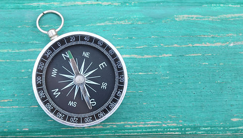 Classic round compass on green wooden vi