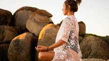Woman meditating at sunset in  Llundadno, Cape Town