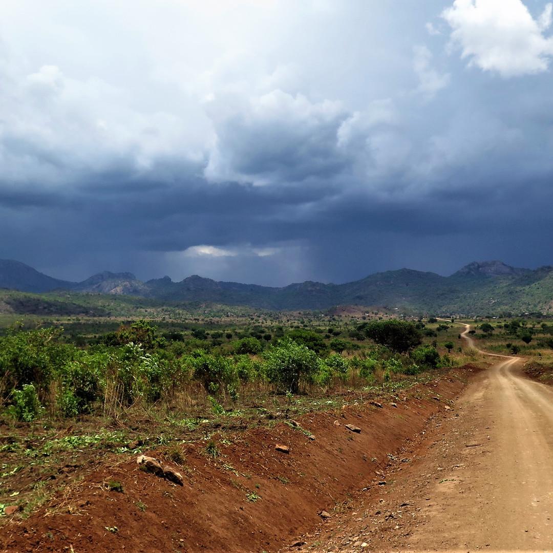 Long road and dark sky in Kidepo National Park, Uganda