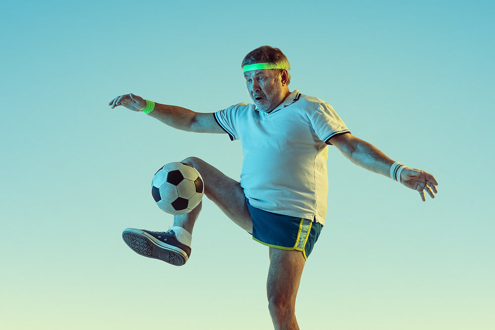Senior man playing soccer, football on g