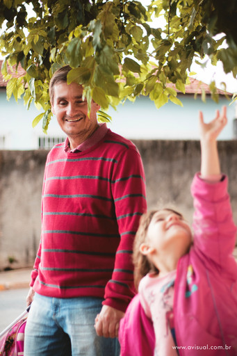 Carla brincando com folhas de arvore no caminho da escola com seu Pai Carlos Trigo