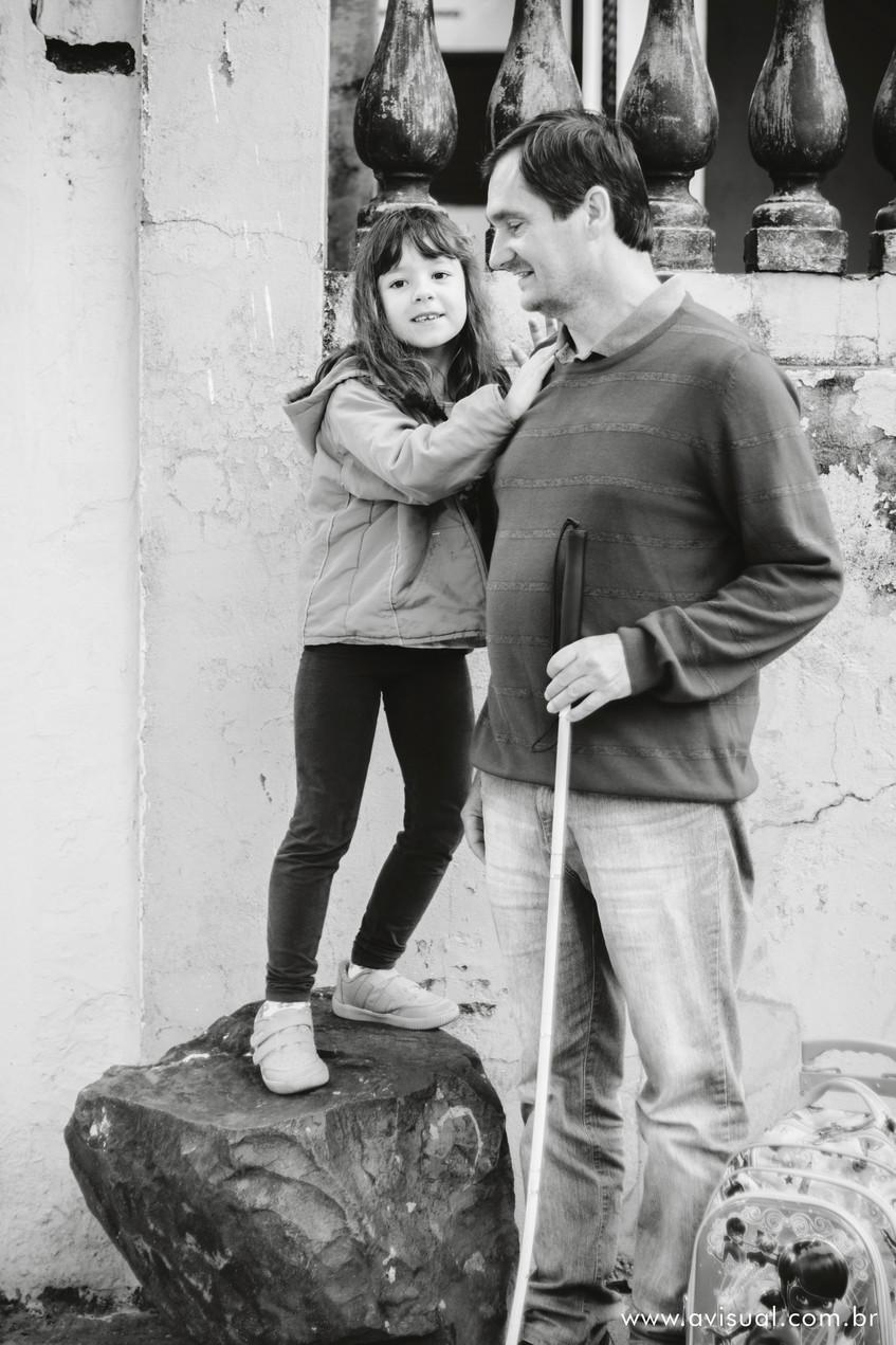Carla ao lado de seu pai Carlos Trigo, em cima de uma pedra na calçada.