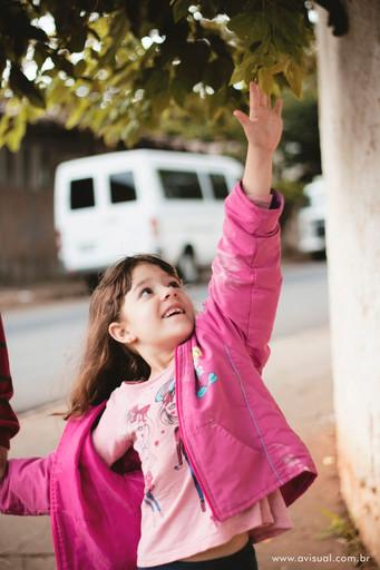 Carla sorrindo em frente ao portao de entrada da escola Criança Feliz