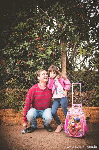 Carlos e Ana Carla sentados em frente ao alambrado de flores da escola Criança Feliz em Botucatu