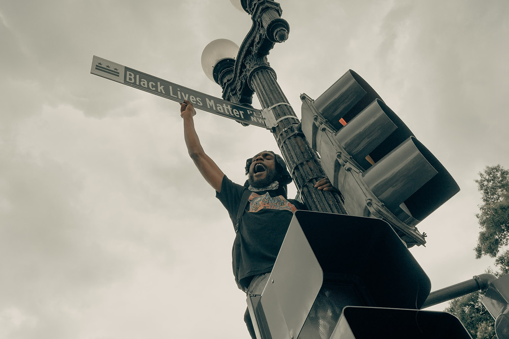 """Photo looks up at a black man standing on a streetlight and triumphantly holding the official street sign, which says """"Black Lives Matter Pl."""""""