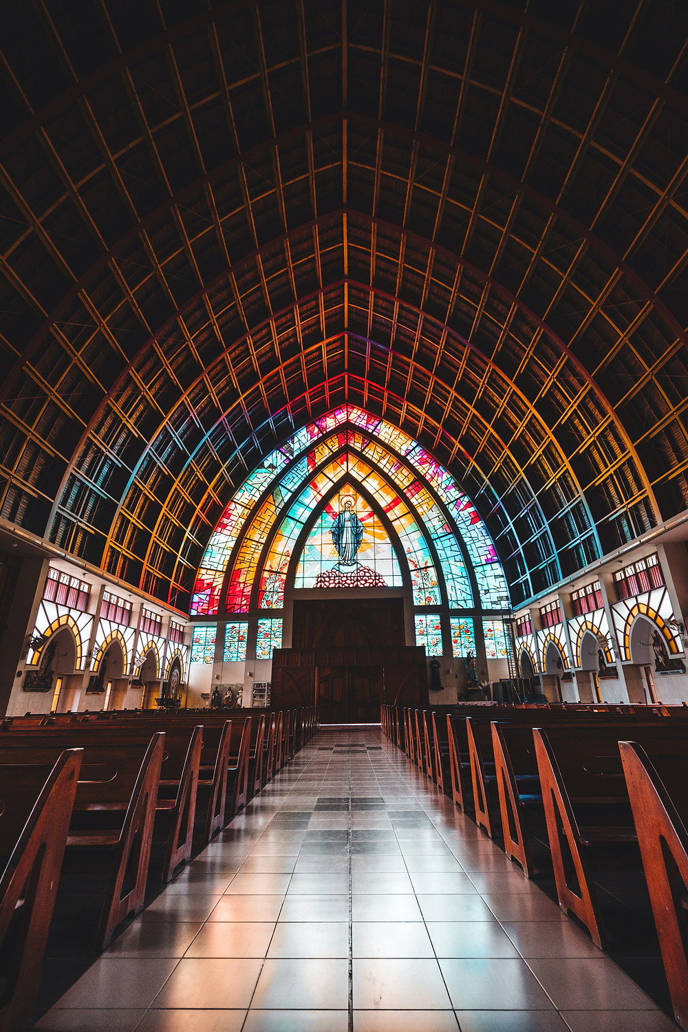 Shot of the inside of a church with wooden pews and a vaulted pyramid roof and a rainbow Christ stained glass window at the back