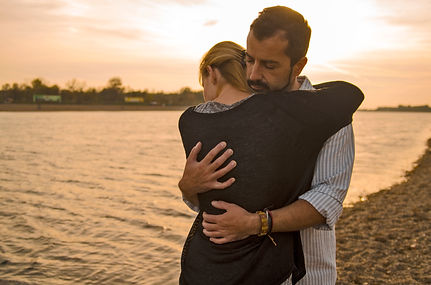 Man and woman hugging in sunset on the b