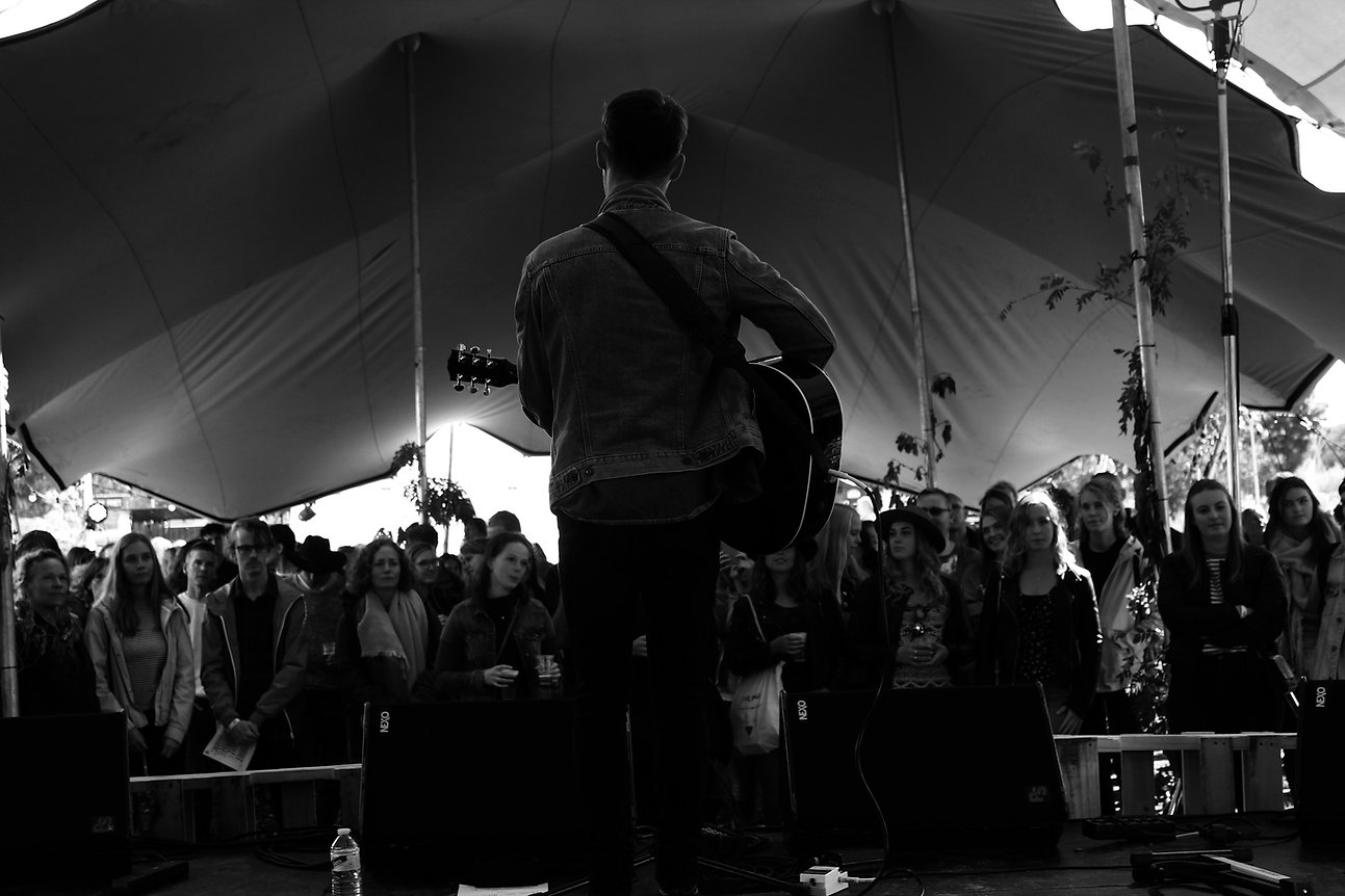 Callum Spencer playing live music on a music festival stage in Amsterdam in black and white