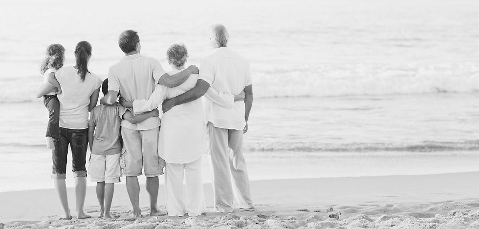 multigenerational family hugging on a beach