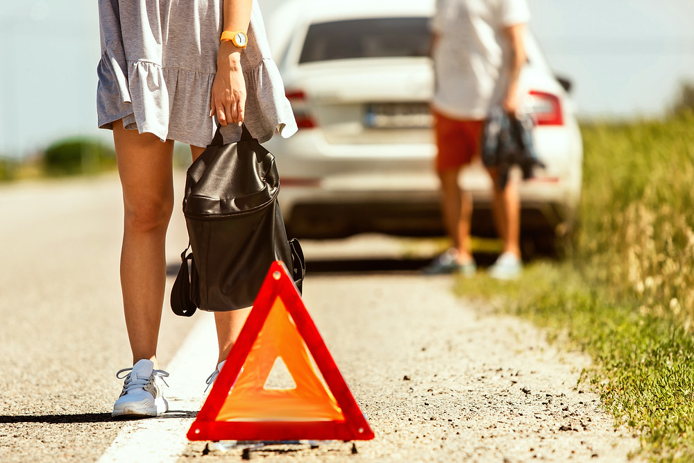 carro quebrado na estrada com triângulo de sinalização e duas pessoas a pé