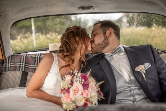 kissing in the wedding car - a special moment for the bridal couple