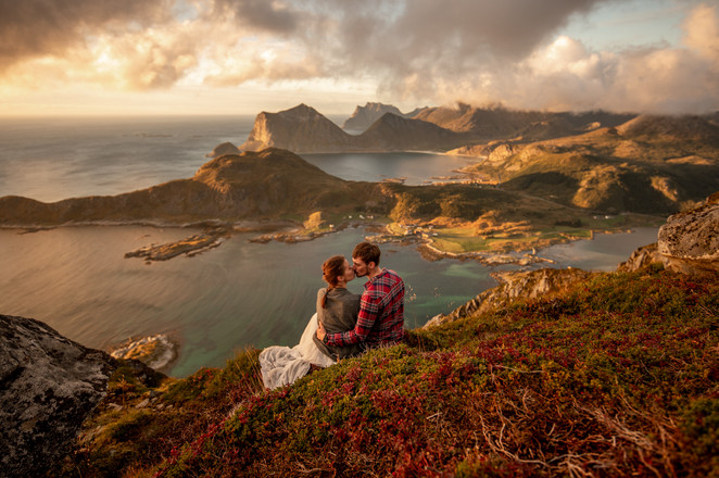 couple kissing in front of an epic landscape