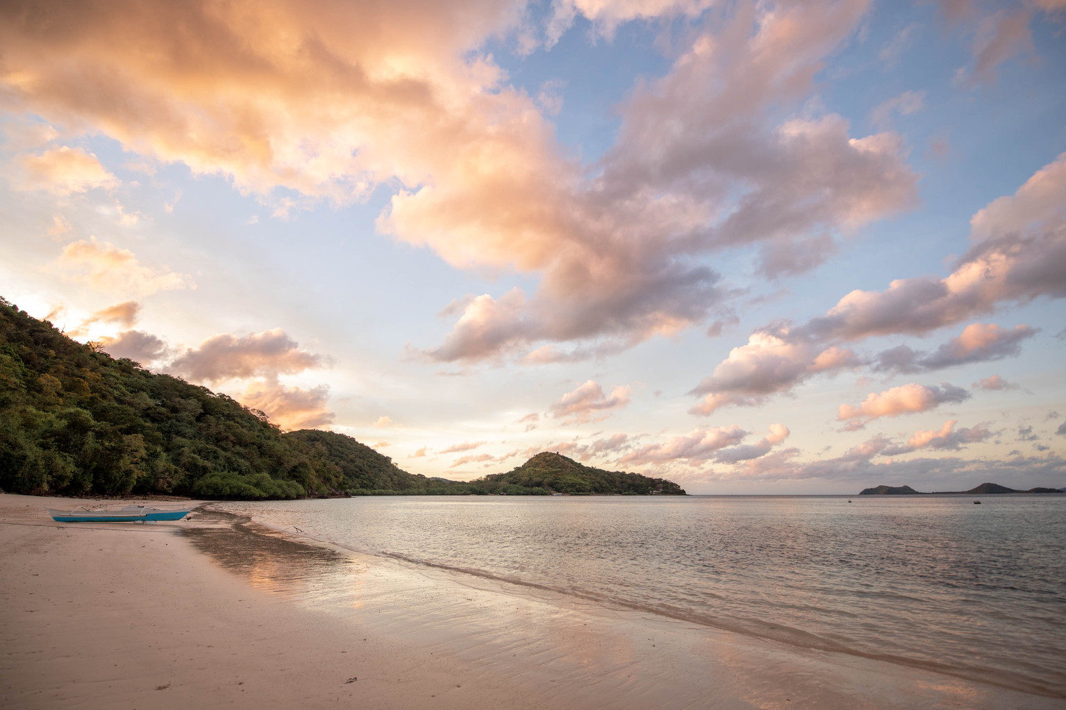 sunrise behind green mountains in the sand in the philippines