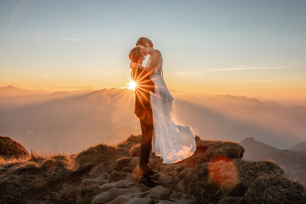 Film kiss at a after wedding session during sunset on a summit in Austria