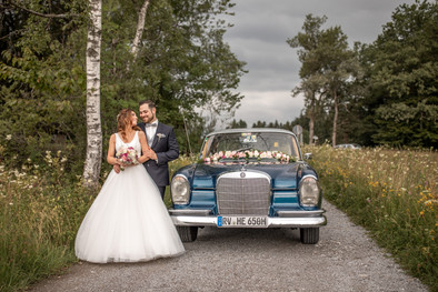 bridal couple with wedding car on a small road in the nature